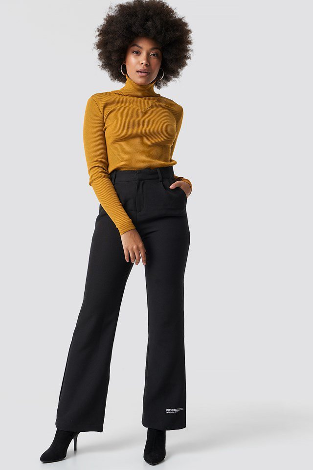 Detailed polo sweater with wide suit pants and black sock boots.